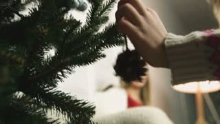 Close up of hands of little girl hanging holiday decorations on beautiful snowy Christmas tree in home interior. Point of view real time full hd video footage.