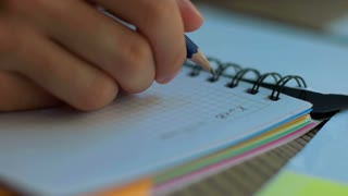 Close up of hands writing on a notebook.