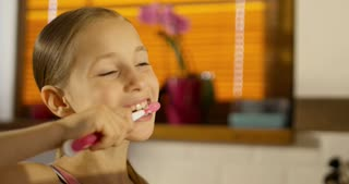 Close-up of little smiling girl brushing teeth in the bathroom