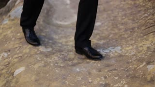 Close-up of man in elegant black shoes walking on the rock background