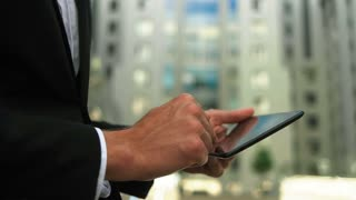 Close up of man s hands using tablet in the street, outdoors portrait.