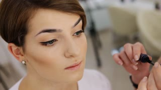 Close-up of separating and curling lashes process with mascara brush, beautiful brunette female model, green eyes