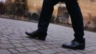 Close up of shoes and pants of a groom walking on the street.