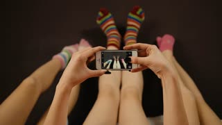 Close up of three friends taking pictures of colorful socks on a black smartphone.