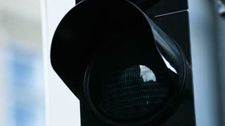 Close-up of traffic light turn green at the daytime. Picture of illuminated green traffic lense light.