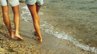 Close up of two barefoot people walking on the beach, woman wearing bracelet on her leg.