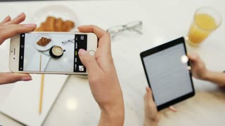 Close-up of two women hands taking photos of food and using tablet computer in the cafe on the white background