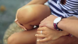 Close up of two young tanned people sitting on the stone and touching each others.