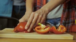 Close up of woman cutting pepper.