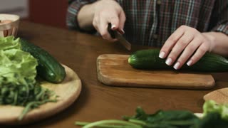Close up of woman`s hands cutting cucumbers on the wooden board.