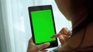 Close up of young brunette woman holding tablet in hands. Green screen Chroma Key. Close up.
