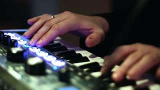 Close-up picture of music artists hands playing on electronic keyboard and  pressing pads on a control desk.