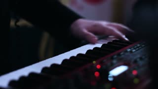 Close-up picture of music performers hands playing on electronic keyboard and turning knobs on a control desk.