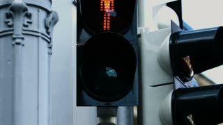 Close-up picture of the traffic light during the day changing from red to green for pedestrians.