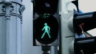 Close-up picture of the traffic light during the day when green lamp starts to blink before it changes to the red symbol and warns pedestrians