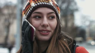Close-up portrait of a funny girl talking on her mobile device outdoors.