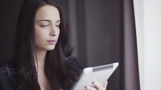 Close-up portrait of a handsome caucasian female in her 20s using tablet indoors.