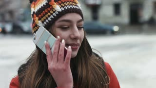 Close-up portrait of an attractive female in her 20s using her cellphone  outdoors.Girl talking on the telephone.
