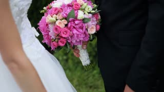 Close up portrait of happy wedding couple holding pink bridal bouquet and gently kissing, outdoors