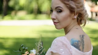 Close up portrait of magical beautiful young bride in elegant dress with bouquet in the park. Looking at camera and smiling