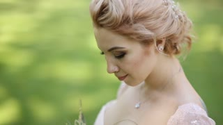 Close up portrait of magical beautiful young bride wearing elegant white dress with bouquet in the park.