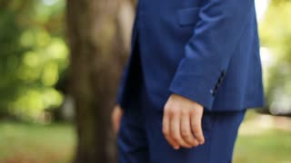 Close up side view of groom in blue suit walking on nature at sunny day