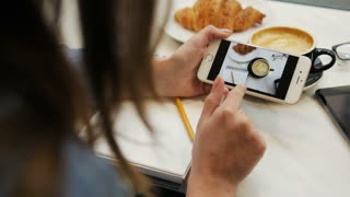 Close-up video of two women looking photo on smartphone in the cafe. Choosing photo. Back view