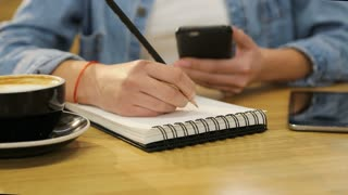 Close up woman hands holding smartphone and writing in notebook in the cafe