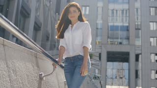 Closeup of sexy brunette woman in white shirt and blue jeans leaning against metal fence at modern street