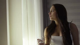 Closeup portrait of beautiful happy smiling young woman drinking fresh pure water fom glass in morning at window