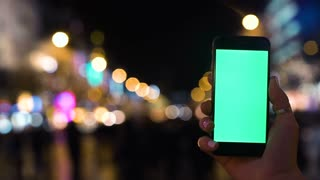 Closeup. Young man is using Smartphone with Green Screen at Evening Time in front of road traffic. Casual Lifestyle. Hroma Key. Close up. Tracking motion. Vertical.