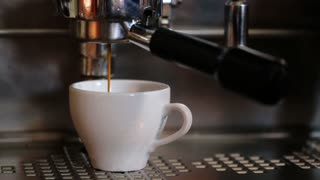 Coffee maker filling espresso in a cup on white and then hand off the coffee machine
