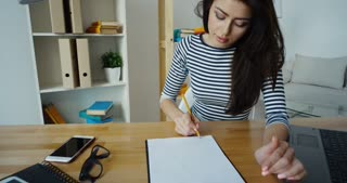 Confident brunette businesswoman in glasses taking note in a notepad at office, close-up
