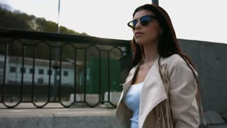 Confident young brunette woman in white jacket and black sunglasses walking down stairs in the city