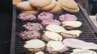 Cook melts cheese on a burger. Cook uses a blow torch to melt cheese on a meat cutlet. Chef melts cheese on a burger using a blow torch.