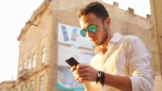 Cool man worn in sunglasses tapping on a touchscreen. Guy using smartphone outdoors
