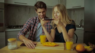 Couple making pictures of oranges in the kitchen.