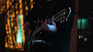 Cropped footage of musician  playing on the guitar on stage during late night show at the nightclub. Medium shot.
