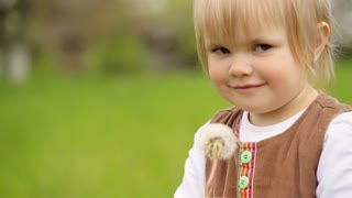 Cute child holding dandelion in her hands and playing with this flower.