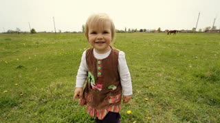 Cute child wearing brown dress running on the grass.