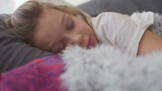 Cute little girl sleeping in bed hugging teddy bear waking up and smiling