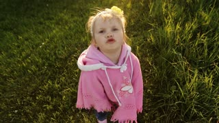 Cute little girl wearing pink clothes posing on camera.