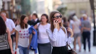 Cute student in black sunglassesin walk in the street and talk on her cell phone