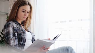 Cute woman wearing blue jeans and grey t-shirt sitting on the table in front of window  and reading a book in her living room.