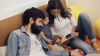 Dad, mom and their young son having fun by playing together on a tablet, they are sitting on a couch in the living room