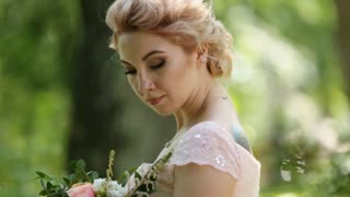 Day dreaming bride - blonde in pink dressand with tattoo poses with bouquet of roses