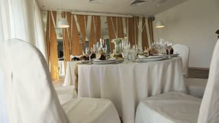 Decorated with white flowers and candles chairs and set tables in the restaurant ready to receive guests