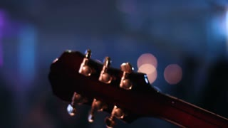 Detail footage of guitar headstock  which is played by musician on a concert. People dancing on a blurred background.