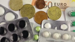 Different Euro money bills on pills and colorful medicine