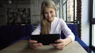 Distance is not a problem. Beautiful cheerful young blonde woman holding her touchpad and waving with her hand while sitting at café